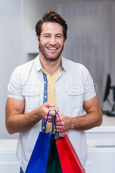 Mosolyog férfi tart bevásárlótáskák portré ruházat Stock fotó © wavebreak_media