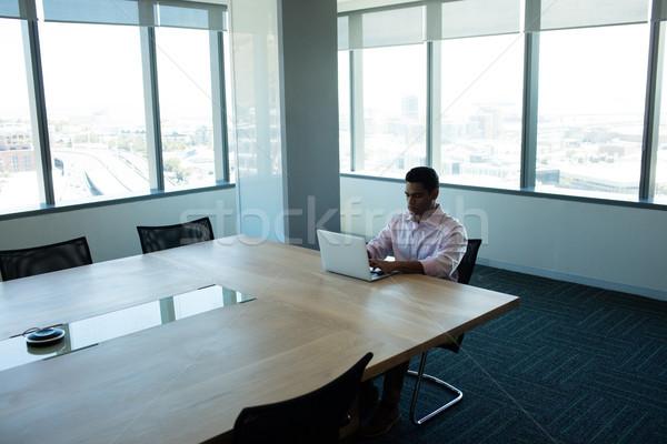 Imprenditore utilizzando il computer portatile sala conferenze seduta tavola computer Foto d'archivio © wavebreak_media