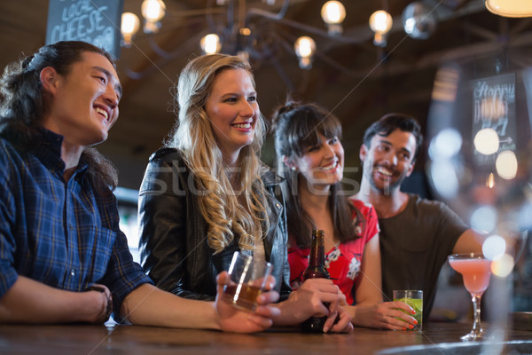 Smiling friends counter looking away in pub Stock photo © wavebreak_media