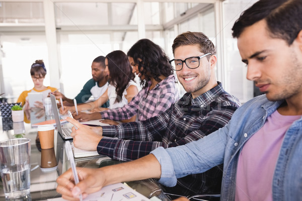Smiling businessman sitting amidst colleagues working at office Stock photo © wavebreak_media