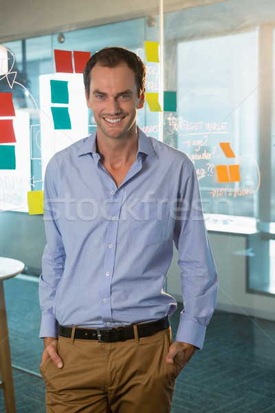 Male executive standing with hands in pocket at office Stock photo © wavebreak_media