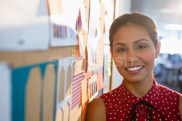Sorridente feminino executivo em pé boletim conselho Foto stock © wavebreak_media