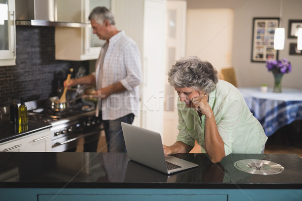 Wife using laptop while husband cooking in kitchen Stock photo © wavebreak_media