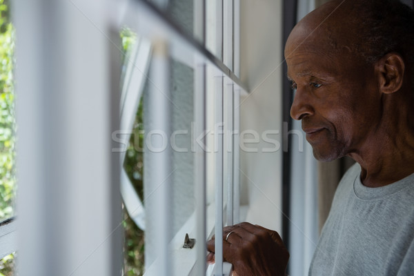 Thoughtful senior man looking out through window Stock photo © wavebreak_media