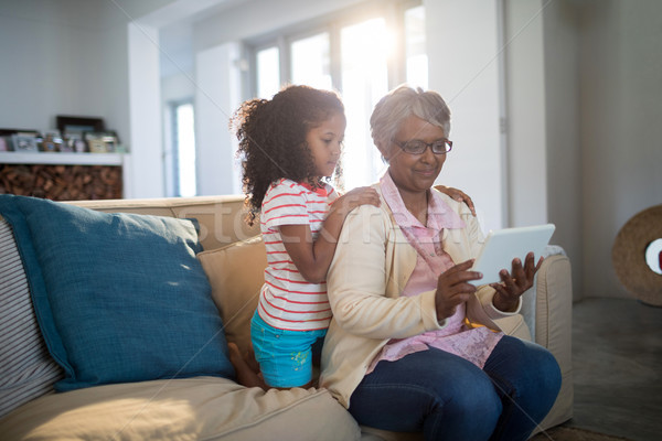 Grandmother and granddaughter using digital tablet on sofa in living room Stock photo © wavebreak_media