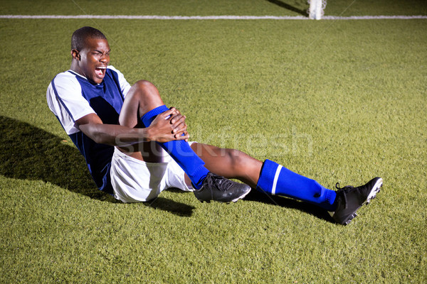 Young male soccer player shouting in agony with knee pain Stock photo © wavebreak_media