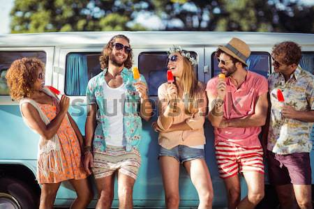Smiling friends standing by camper van at campsite Stock photo © wavebreak_media