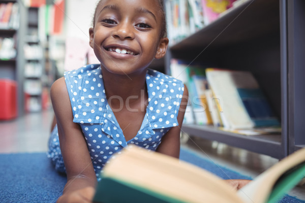 Portrait of smiling girl with book in library Stock photo © wavebreak_media