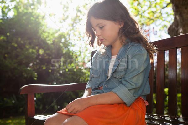 Sad girl sitting on wooden bench against plants Stock photo © wavebreak_media