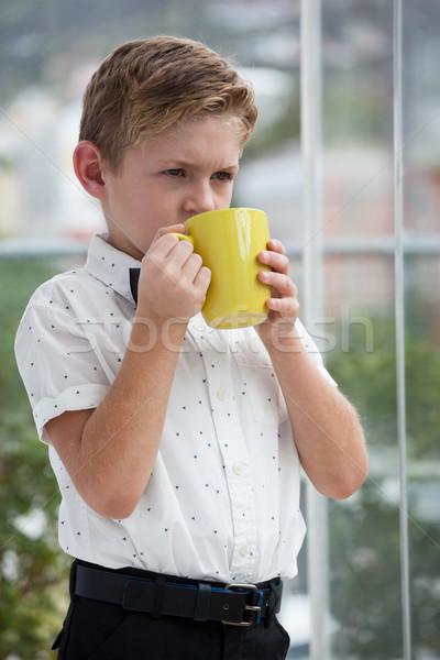 Thoughtful businessman looking away while holding yellow mug Stock photo © wavebreak_media