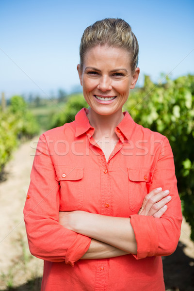 Smiling woman standing with hands on hip in vineyard Stock photo © wavebreak_media