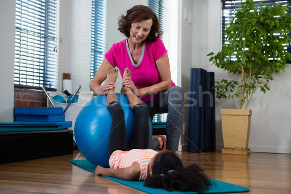 Female physiotherapist helping girl patient in performing stretching  exercise on exercise mat Stock photo © wavebreak_media