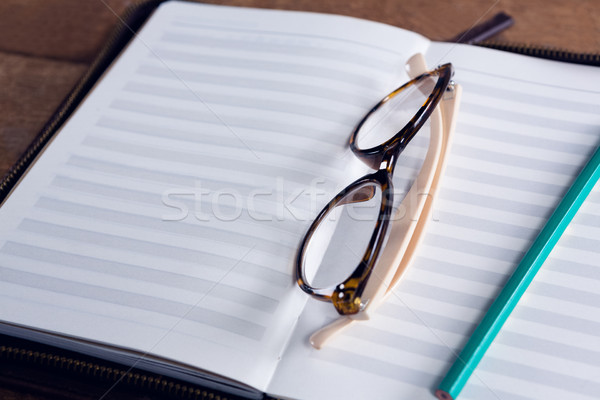 Close-up of spectacles and pencil on organizer at table Stock photo © wavebreak_media
