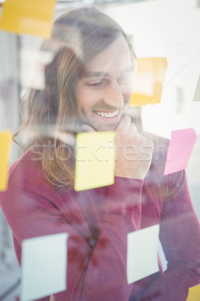 Businessman with hand on chin looking at sticky notes Stock photo © wavebreak_media