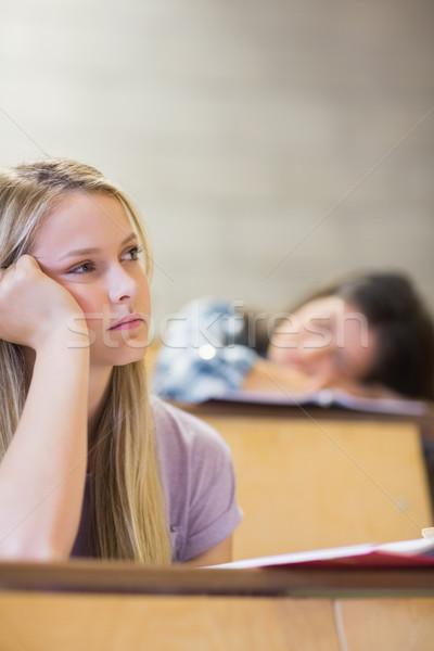 Bored student listening while classmate sleeping Stock photo © wavebreak_media