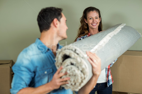 Happy couple carrying rolled up rug Stock photo © wavebreak_media
