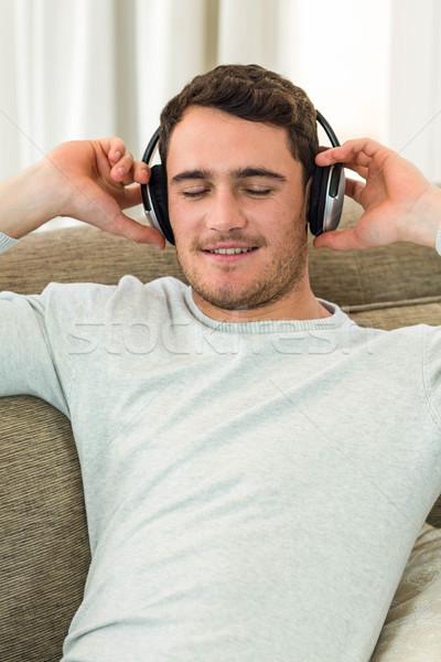 Joven sentimiento escuchar música auriculares salón Foto stock © wavebreak_media
