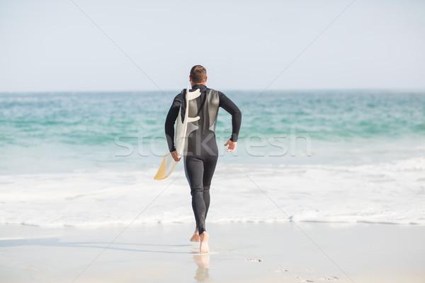 Surfer piedi mare tavola da surf spiaggia Foto d'archivio © wavebreak_media