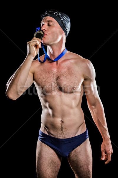 Swimmer kissing his gold medal Stock photo © wavebreak_media