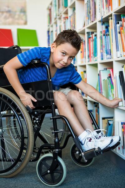 Portré fogyatékos fiú keres könyvek könyvtár Stock fotó © wavebreak_media