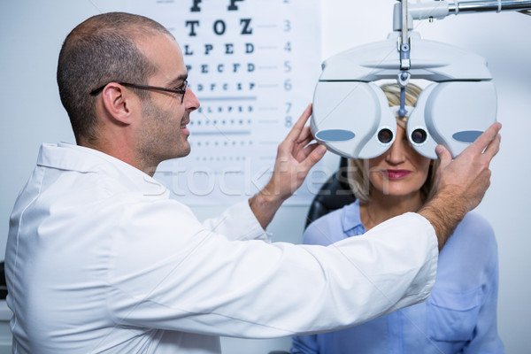 Smiling optometrist examining female patient on phoropter Stock photo © wavebreak_media