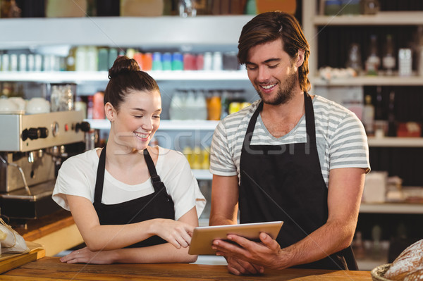 Smiling waiter and waitress using digital tablet at counter Stock photo © wavebreak_media