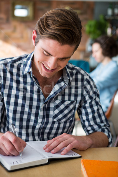 Stock photo: Man writing notes in diary in coffee shop