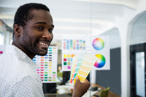 Graphic designer holding color swatch Stock photo © wavebreak_media