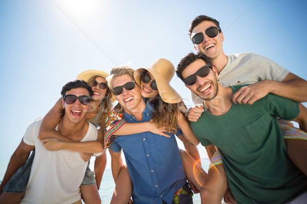 Men piggybacking friends against sky Stock photo © wavebreak_media