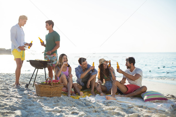 Friends having drinks by barbecue at beach against sky Stock photo © wavebreak_media