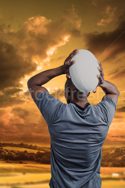 Composite image of rear view of sportsman throwing rugby ball Stock photo © wavebreak_media