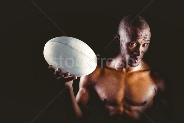 Portrait of confident shirtless sportsman holding rugby ball Stock photo © wavebreak_media