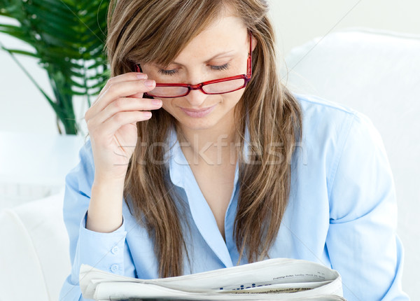 Enthusiastic woman with glasses reading a newspaper Stock photo © wavebreak_media