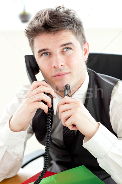 Stock photo: Thoughtful businessman talking on phone sitting in his office
