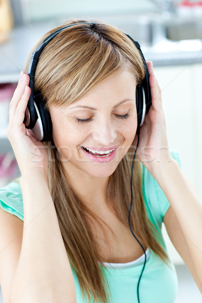 Animated caucasian woman listen to musik with headphones  in the kitchen Stock photo © wavebreak_media