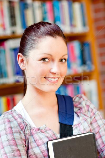 Joyful young caucasian woman holding a book in a bookstore Stock photo © wavebreak_media