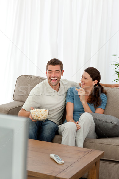 Cheerful couple eating pop corn while watching a comic movie Stock photo © wavebreak_media