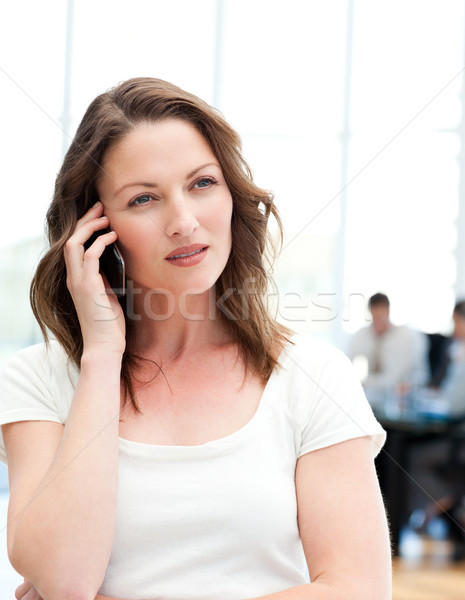 Pensive businesswoman on the phone while her team is working in the background Stock photo © wavebreak_media
