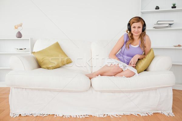 Di bell'aspetto donna ascoltare musica posa seduta divano Foto d'archivio © wavebreak_media