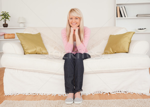 Beautiful blonde woman posing while sitting on a sofa in the living room Stock photo © wavebreak_media