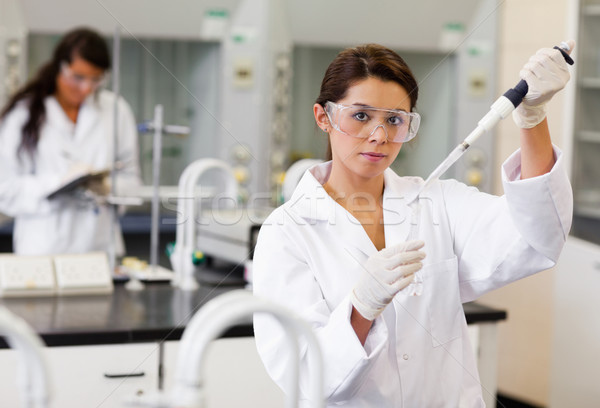Student pouring a liquid in a tube during a lecture Stock photo © wavebreak_media