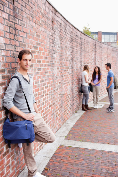Portrait of a student leaning on a wall while his friends are talking outside a building Stock photo © wavebreak_media