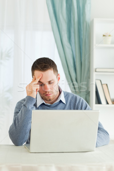Worn out young businessman on his laptop in his homeoffice Stock photo © wavebreak_media