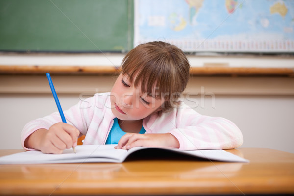 Focused girl writing in a classroom Stock photo © wavebreak_media