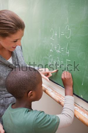 Cute teacher and a pupil making an addition on a blackboard Stock photo © wavebreak_media