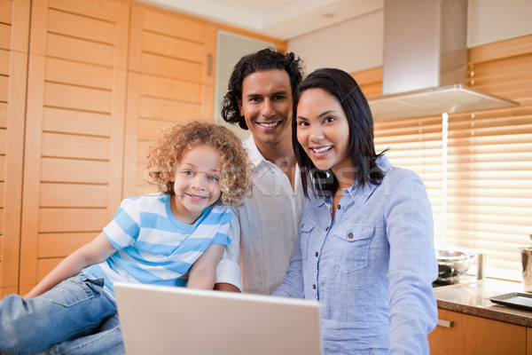 Cheerful young family surfing the internet in the kitchen together Stock photo © wavebreak_media