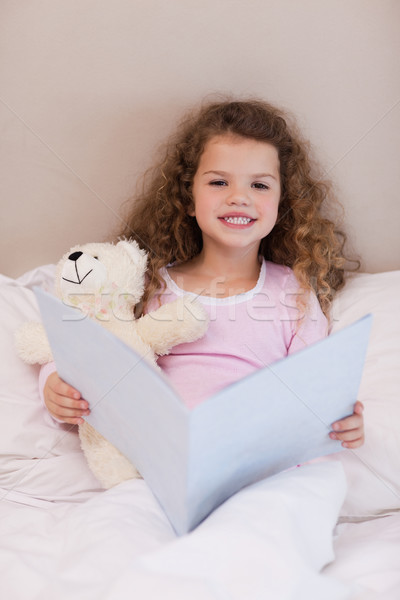 Little girl sitting on the bed with a book Stock photo © wavebreak_media