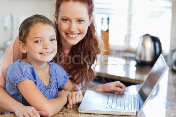 Mother and daughter together with notebook in the kitchen Stock photo © wavebreak_media