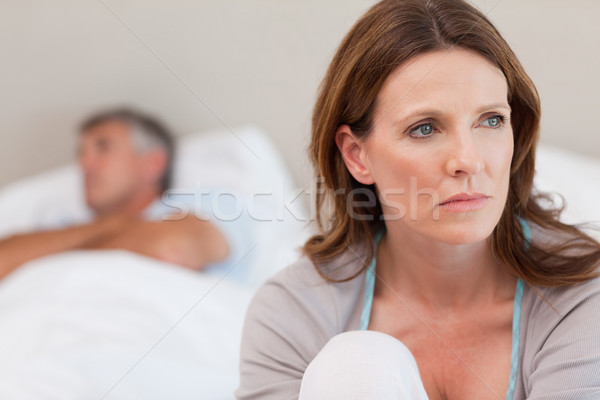 Sad mature woman on bed with her husband in the background Stock photo © wavebreak_media