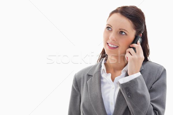 Close up of a businesswoman looking up while smiling on the phone against white background Stock photo © wavebreak_media